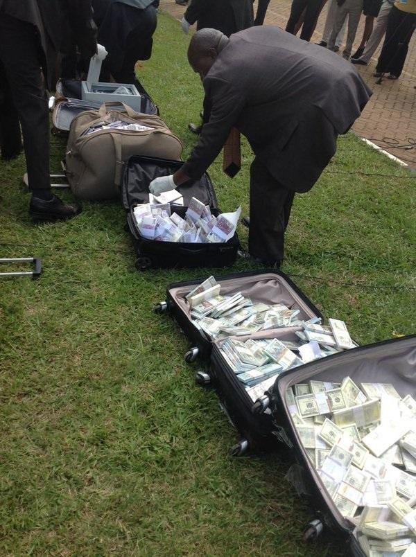 Nairobi police inspecting the bundles of fake note stacks found in suitcases